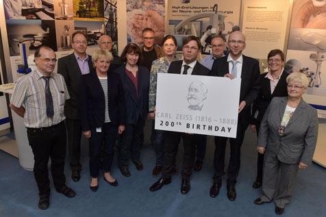 Jörg Nitschke, Leiter der Unternehmenskommunikation von ZEISS (links), und Wilfried Röpke, Geschäftsführer von JenaWirtschaft, präsentieren gemeinsam mit Partnern aus Jena das Signet, dass  ZEISS  anlässlich des 200. Geburtstages seines Gründers am 11. September 2016 gestaltet hat.