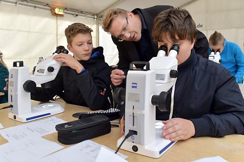 ZEISS Mikroskopie-Workshop: Dr. Michael Zölffel, Mikroskopspezialist von ZEISS, unterstützt Nick Süßenguth und Jonas Blobelt (links) von der Staatlichen Grund- und Gemeinschaftsschule Tanna beim Mikroskopieren.