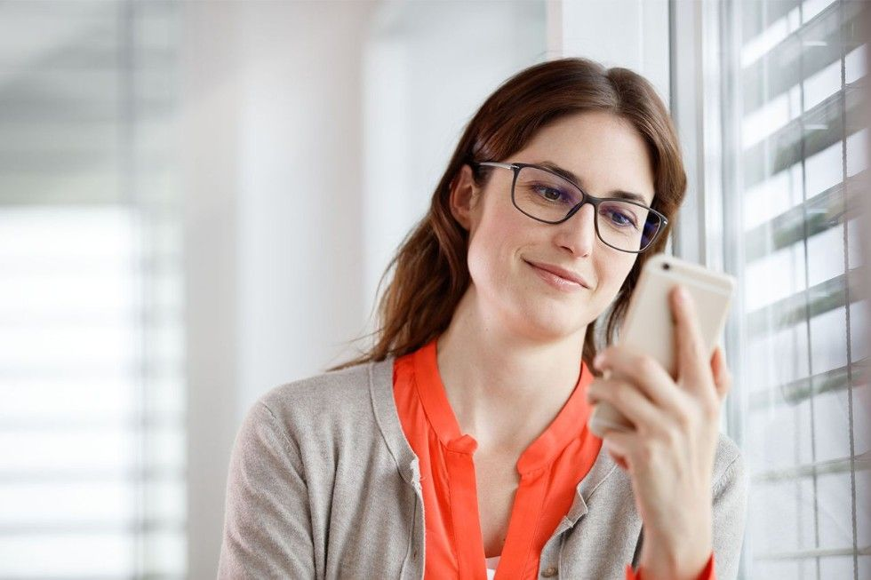 Woman with glasses looking at her smartphone